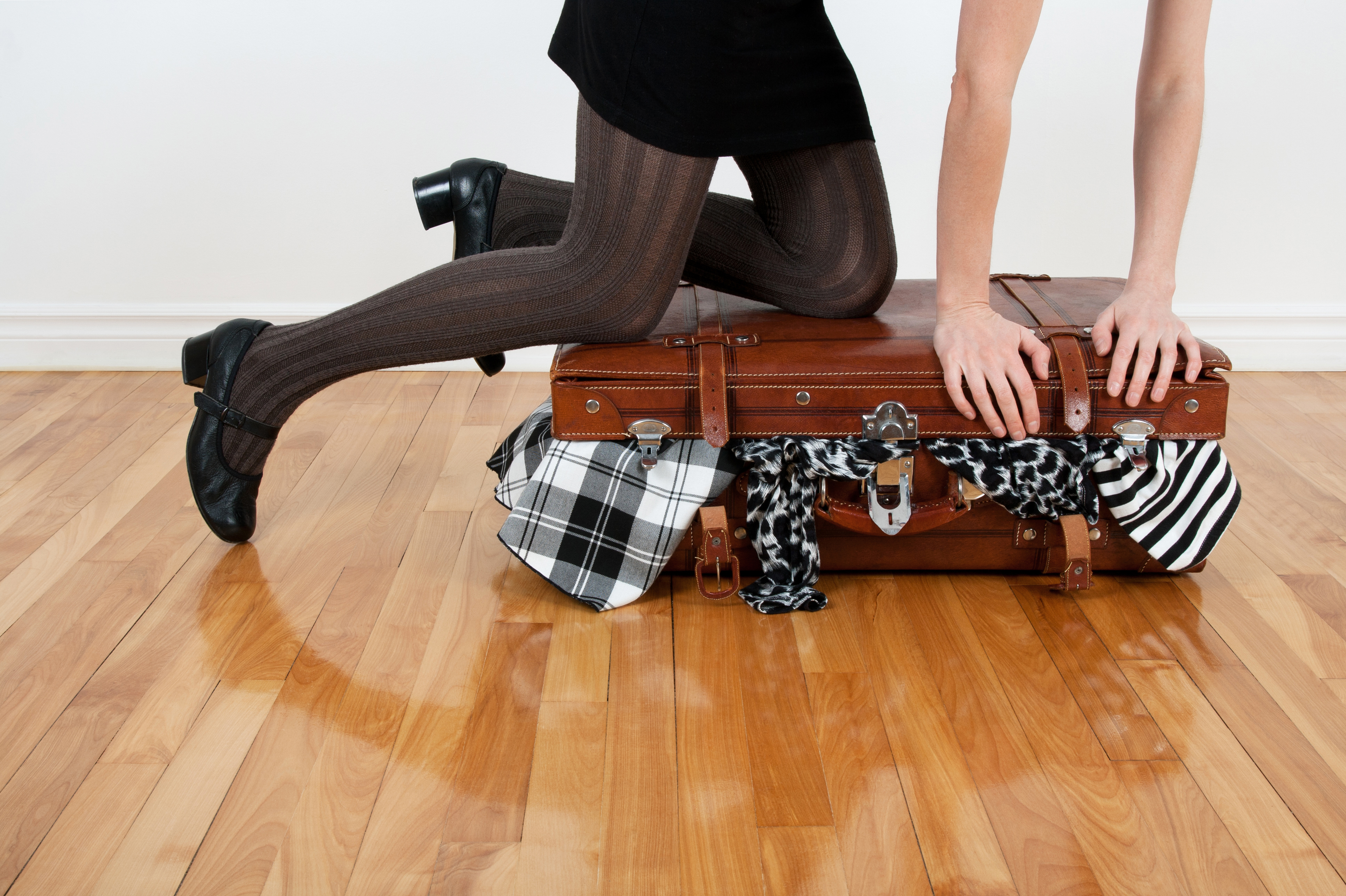 Woman packing overfilled suitcase